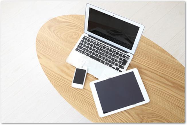 木のテーブルに置かれたパソコンやスマホなどの電子機器