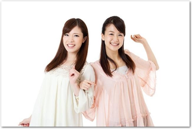 笑顔で腕を絡ませる2人組の女性の様子