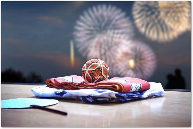 縁側に置かれた浴衣と団扇と手毬の向こうに打ち上げ花火が見える光景