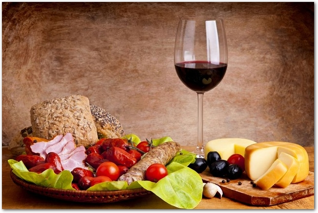 グラスに注がれた赤ワインとチーズや肉などの食材