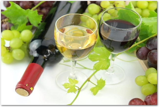 ワインボトルとぶどうの真ん中に置かれたグラスに入った赤と白のワイン