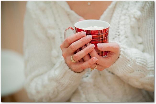マグカップを両手で包み込むように持つ白いニット姿の女性の手のアップ