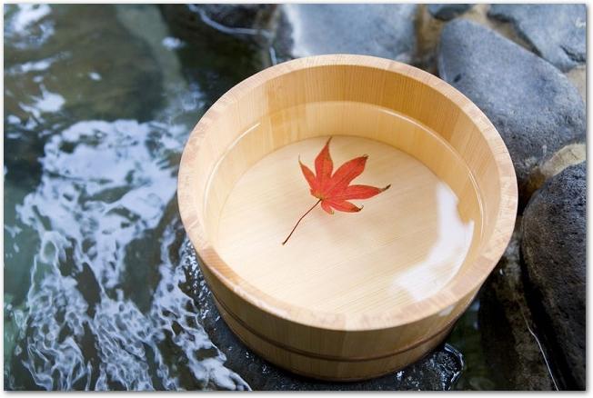 露天風呂の浴槽に紅葉の葉が浮かべられた木桶がある様子
