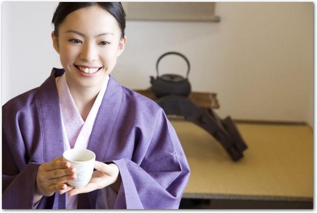 温泉旅館の客室でお茶を飲みながらくつろぐ浴衣姿の女性の様子