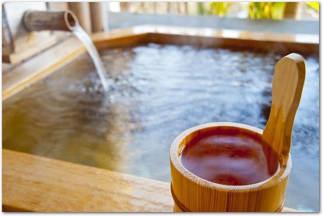 檜風呂の温泉とお湯の入った木の湯桶