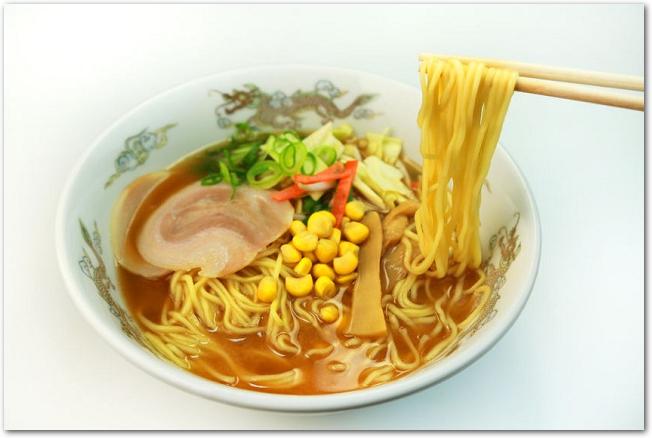 コーンやチャーシューの乗った味噌ラーメンの麺を箸で持ち上げている様子