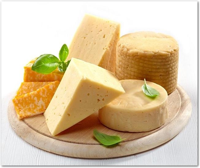 様々な種類のチーズが円形の木皿の上に乗っている様子