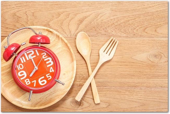 木のカトラリーとお皿の上に赤い目覚まし時計が乗っている様子
