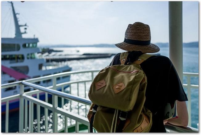 フェリーのデッキから海を眺めている旅行者の後ろ姿