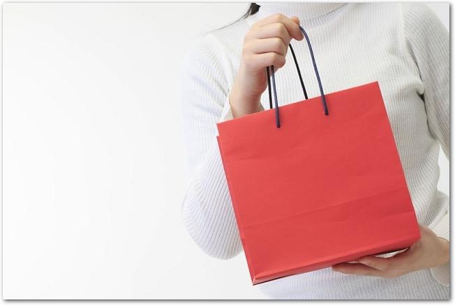 赤い紙袋を持っている女性の手元の様子