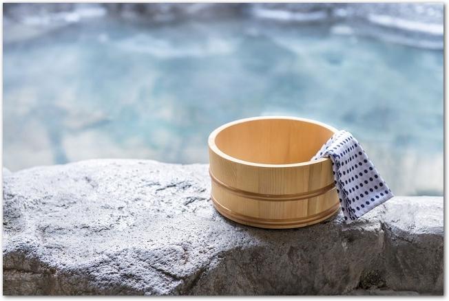 露天風呂の縁に手ぬぐいの入った木桶が置いてある様子