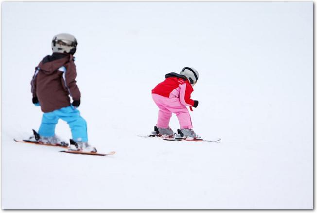 スキーを滑る2人の小さい子どもの後ろ姿