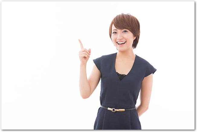 指を指す笑顔の若い女性の様子
