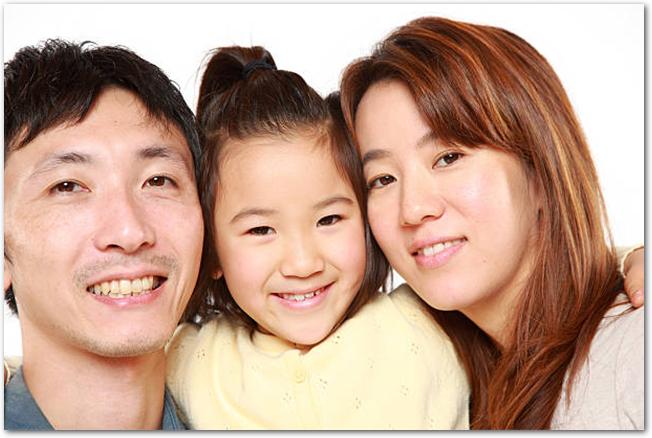 両親とその間にいる女の子が笑っている様子