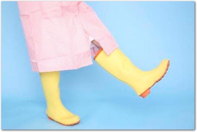 雨合羽と長靴を身につけた女性の足元