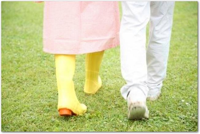 雨の日に芝生の上を歩くカップルの足元