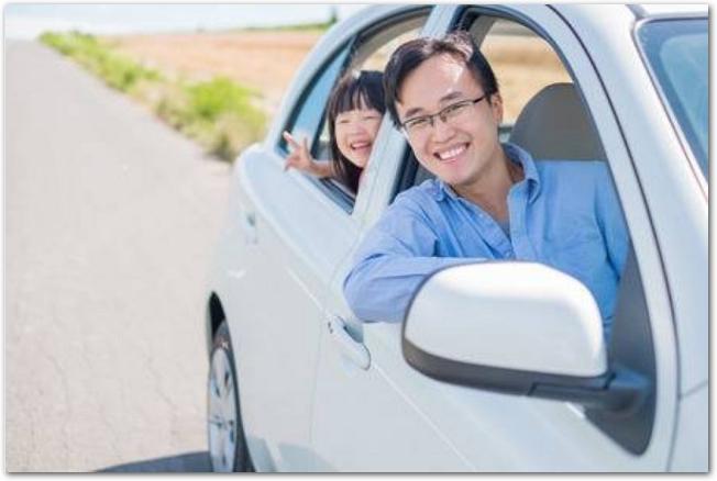 レンタカーの窓から顔を出す父親と娘の様子